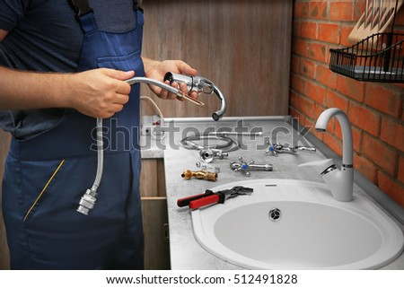 Plumber replacing faucet in kitchen, close up view