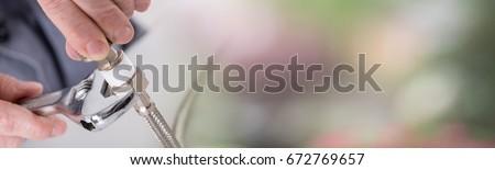 Plumber screwing plumbing fittings, blurred background