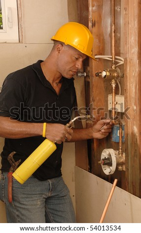Plumber sweating a copper pipe with a propane torch