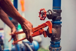 Plumber using a wrench to repair and remove the water supply pipe and valve. Plumbers working using orange pipe wrenches with blurry motor pump motor.