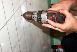 Plumber using grungey old drill to drill hole on vintage bathroom tile - closeup of hands