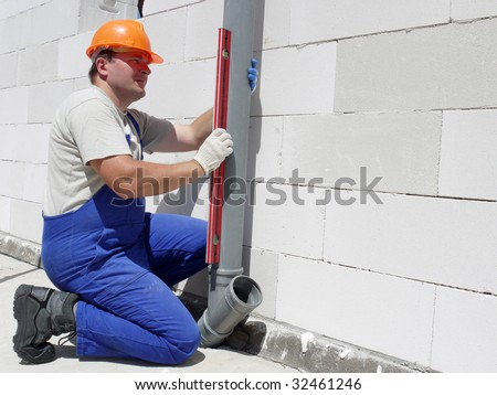 Plumber using level for checking plumb line of assembled pvc sewage pipes inside unfinished house