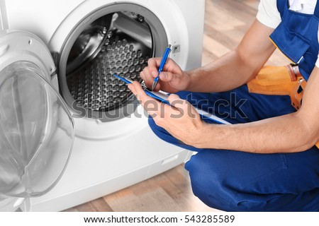Plumber with clipboard near washing machine