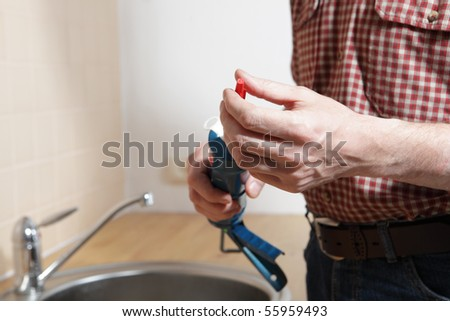 Plumber with silicone sealant in a caulking gun