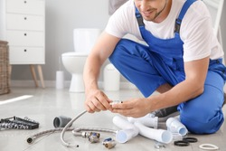 Plumber with tools working in restroom