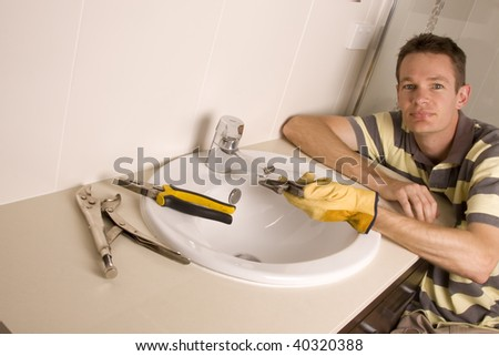 Plumber working on a broken tap in a bathroom sink
