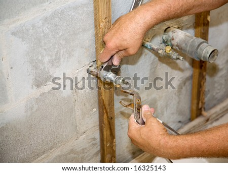 Plumbers hands using a wrench and pliers to loosen a pipe.  Closeup with room for text.  Authentic and accurate content depiction.