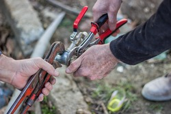 Plumbers working using pipe wrenches at outdoor