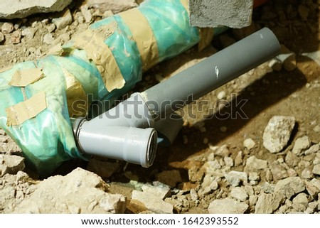 Plumbing and piping work, sewer pvc pipes are close to the ground and ready for isolation to be protected when they will be covered with ground and stones.