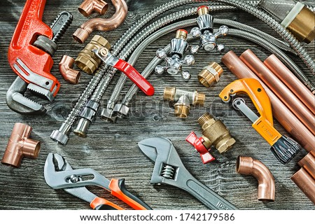 plumbing concept big set of piping accessories monkey and plumb adjustable wrenches copper brass fittings pipe cutter on vintage wood background
