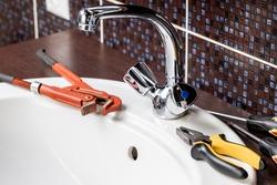 plumbing faucet repair concept. plumber using wrench tool and pliers to adjusting tap leak at bathroom. diy plumber conceptual.