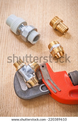 plumbing fixtures and adjustable wrench on wooden board