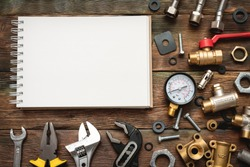 Plumbing flat lay background with copy space. Work tools, pipeline equipment and blank page notepad on plumber workbench. Fix list mockup.