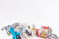 Plumbing parts, accessories and tools on a white background with copy space.