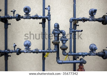 plumbing pipes on  rough wall / abstract grungy background - stock photo