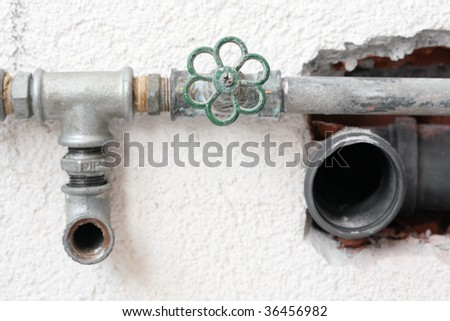plumbing pipes with valve embedded in wall