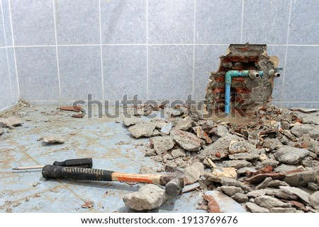Plumbing problems. A wall of a bathroom is opened to find a leak from a pipe leaving rubble on the floor. Foto stock ©