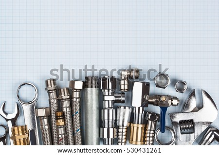 Plumbing supplies on top of blue graph paper.