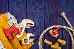 Plumbing tools in yellow bag and spare parts on blue wooden boards are used to replace or repair