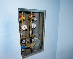 Plumbing, water supply system. Water meters. Modern installation on plastered blue walls background.