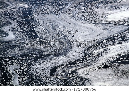 Plume of foam floating on rapid river. Constantly changing macro pattern, stochastic process, connecting statics (microlevel) and dynamics (macrolevel). View from top. Result of water pollution Stockfoto ©