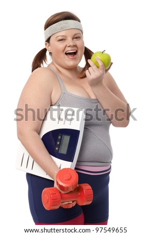 Plump woman biting green apple, holding dumbbells and scale, dieting, smiling.