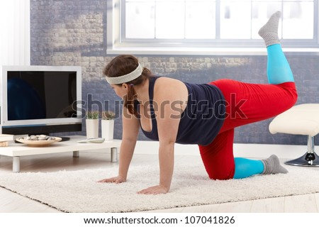 Plump woman exercising at home on floor.