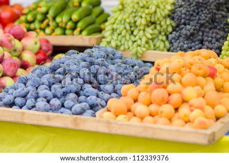 Plums, apricots, apples, cucumbers, grapes in city market