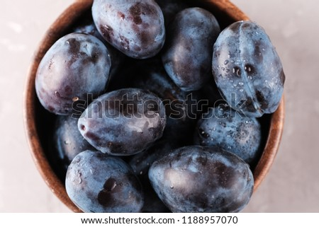 Plums. Fresh ripe washed plums in a wooden bowl close-up on a neutral background.