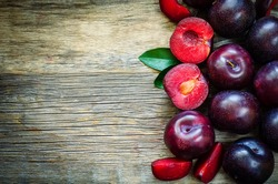 plums on a dark wood background. toning. selective focus on plum with a stone.
