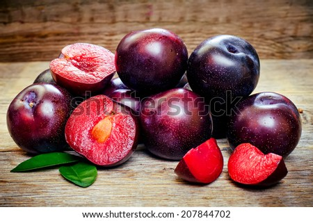 plums on a dark wood background. toning. selective focus on plum with a stone. #207844702