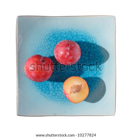 plums on blue square plate, isolated