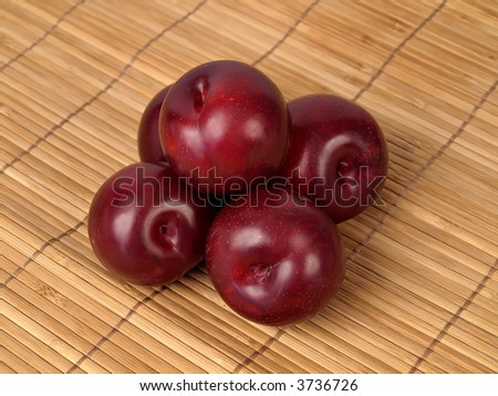 Plums setting on a tan place mat - stock photo