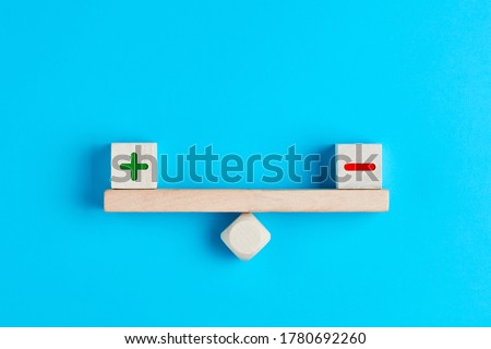 Plus and minus or positive and negative symbols on wooden blocks are in balance on a wooden seesaw. Blue background, flat lay view. Pros and cons equilibrium in decision making under uncertainity.  Stockfoto ©