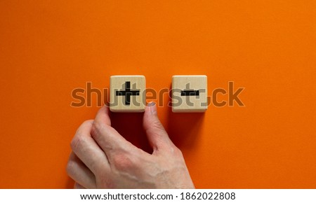 Plus or minus. Businessman holds a cubes with plus icon. Wooden cube with minus icon. Beautiful orange background. Copy space. Business and plus and minus concept. Stockfoto ©
