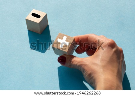 Plus or minus. Woman holds a cubes with plus icon. Wooden cube with minus icon. Beautiful blue background. Business and plus and minus concept. Stockfoto ©