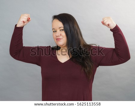 Plus size adult woman flexing biceps or clenching fist with joy, happy successful female with arms up. Success positive emotions.