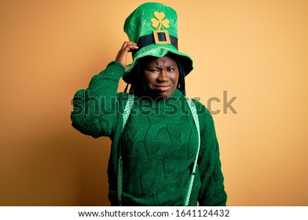 Plus size african american woman with braids wearing green hat with clover on st patricks day confuse and wonder about question. Uncertain with doubt, thinking with hand on head. Pensive concept.