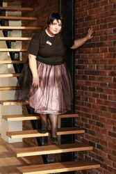 Plus size brunette girl in a lush tulle skirt going down the stairs