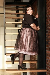 Plus size brunette girl in a lush tulle skirt posing on the stairs