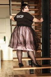 Plus size brunette girl in a lush tulle skirt posing on the stairs With an inscription on a T-shirt film director