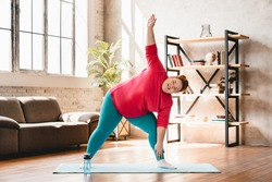 Plus size corpulent young woman doing physical exercises indoors for being in good shape. Dieting and healthy lifestyle for burning fat and calories