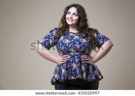 Plus size fashion model in casual clothes, fat woman on beige studio background, overweight female body
