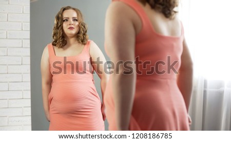 Plus-size female looking in mirror, upset about her weight, suffer insecurities ストックフォト ©