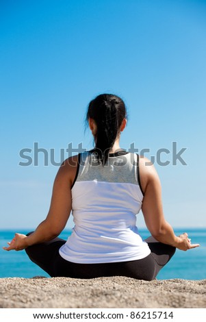 Plus size female practice yoga outdoor under blue sky