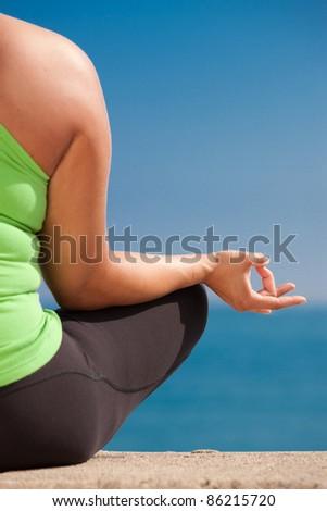 Plus size female practice yoga outdoor under blue sky