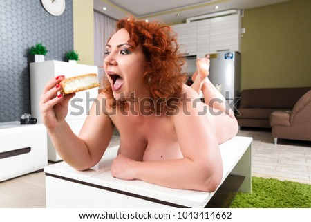 Plus size girl greedy eats sweet pie. Hungry fat model lie on table and eating dessert. Weight loss concept.  red curly hair overweight women with delicious cake