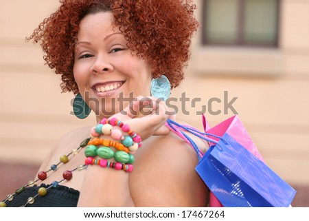 Plus size model, smiling about a purchase and holding a shopping bag.