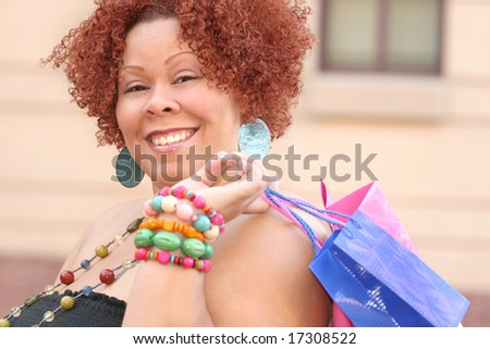 Plus size model, smiling about a purchase and looking into a shopping bag.