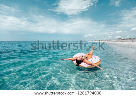 Plus size woman chilling on lilo in the sea water. Girl relaxing on inflatable ring on the beach. Summer vacations, idyllic scene. #1281794008